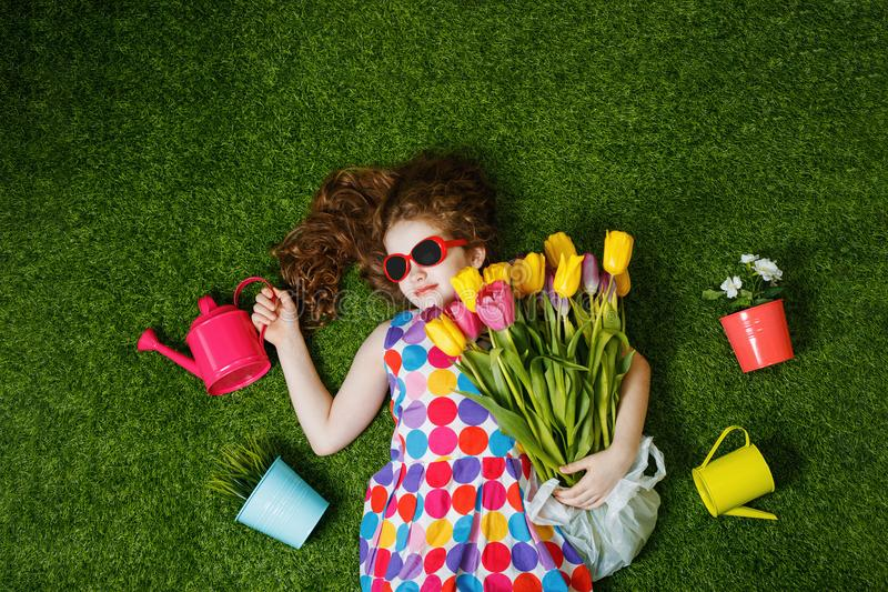 Little curly girl with bouquet of tulips lying in green lawn. royalty free stock image