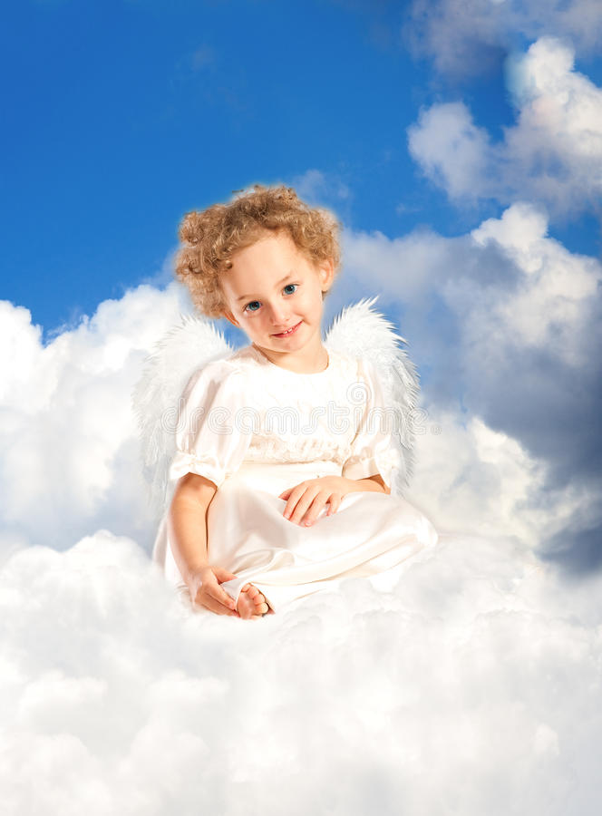 Little curly girl with fairy wings lies on a cloud stock photography