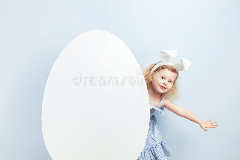 Little curly girl in the light-blue dress with bunny ears on her head looks out from behind a big white egg against a. Blue wall. Easter bunny stock photos