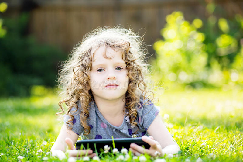 Little curly girl lying on the grass and holds in hands tablet. royalty free stock photos