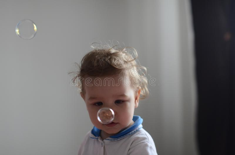 Girl playing with soap bubbles stock images