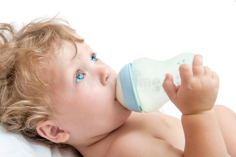 Little curly-headed baby sucks a bottle royalty free stock photography