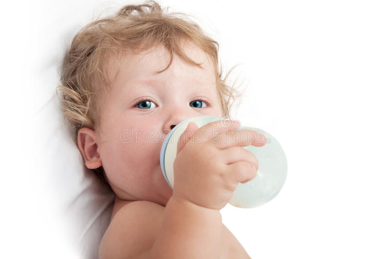 Little curly-headed baby sucks a bottle of milk. On a white background royalty free stock photos