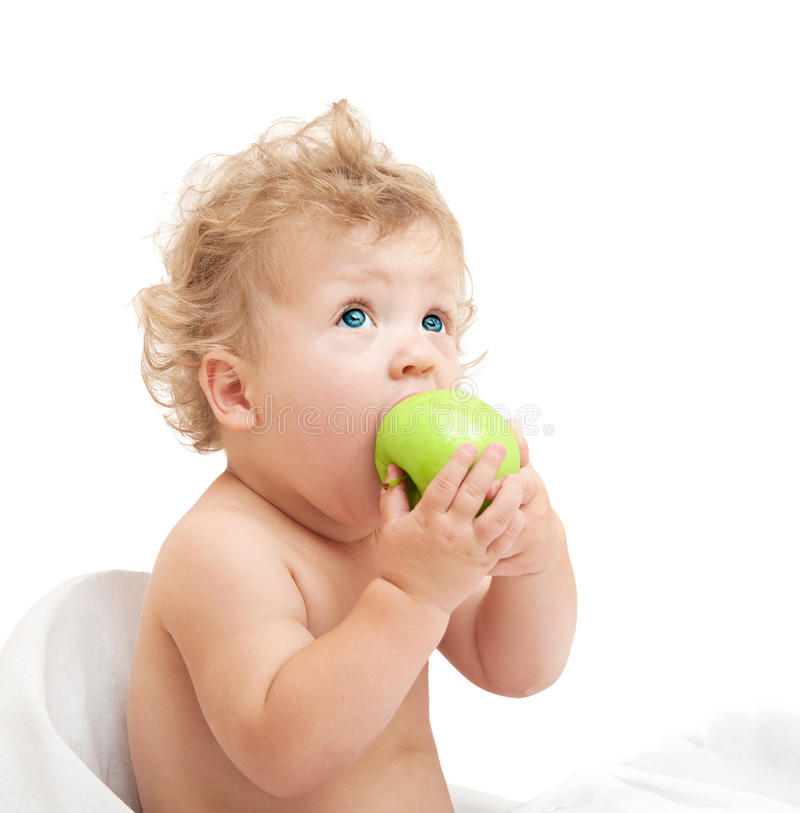 Little curly-headed child eats a green apple and looking up stock photography