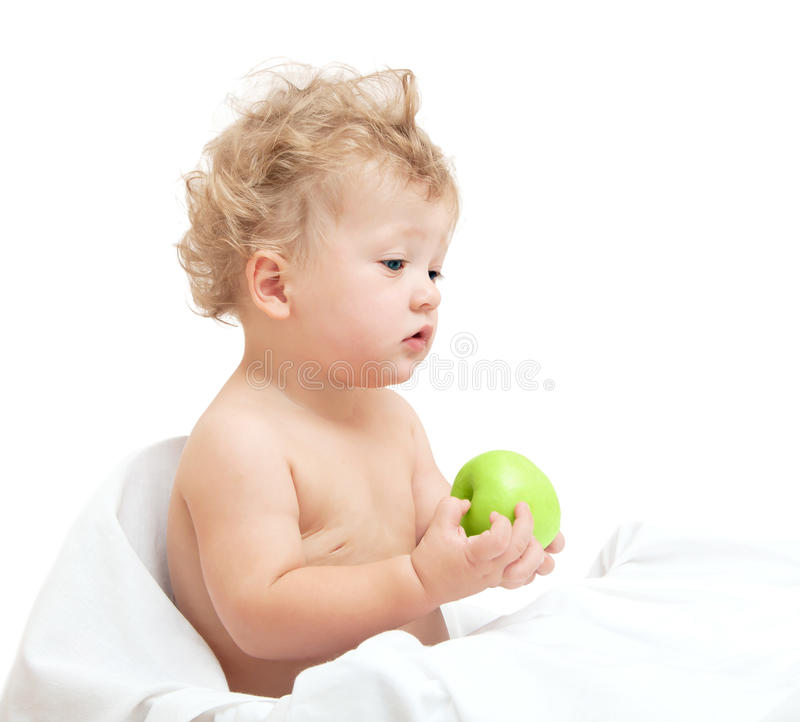 Little curly-headed child holding a green apple royalty free stock photo
