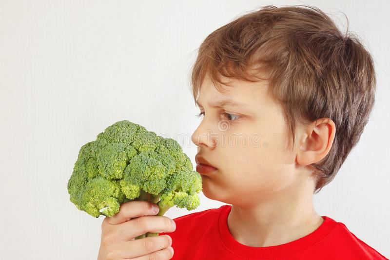 Little cut boy in a red shirt with broccoli on white background royalty free stock photo