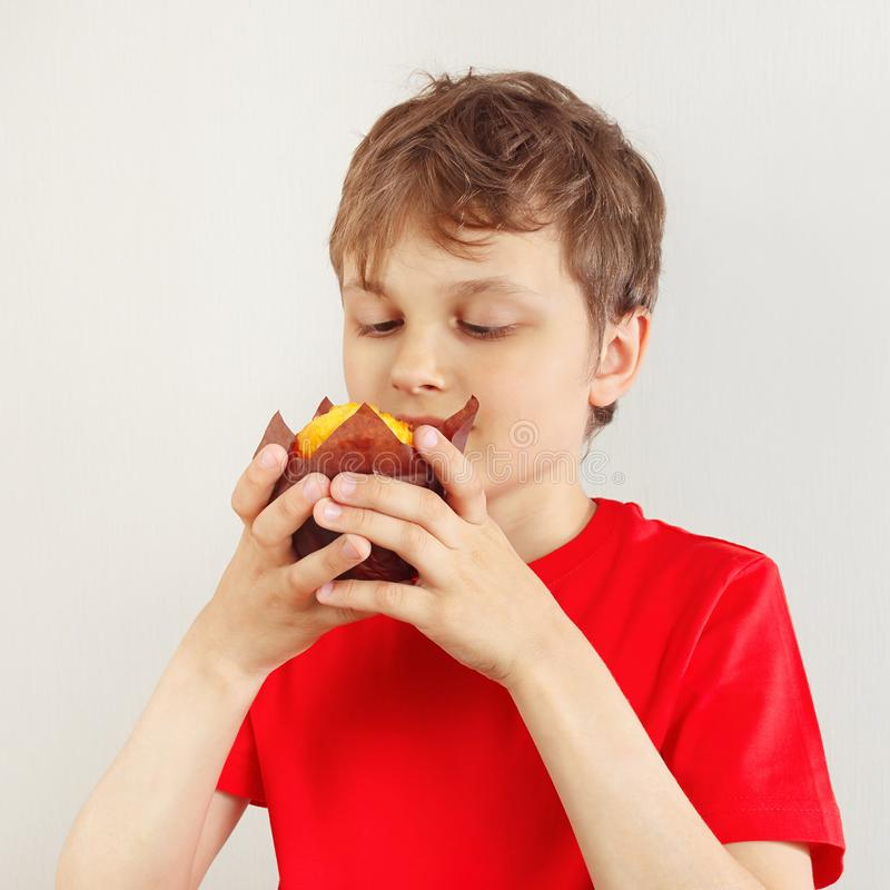 Little cut boy in a red shirt with muffin on white background royalty free stock images