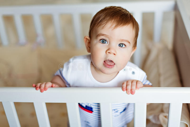Little cute adorable little blond boy in a striped bodykit is in. The nursery with white crib and stares into the camera royalty free stock photography