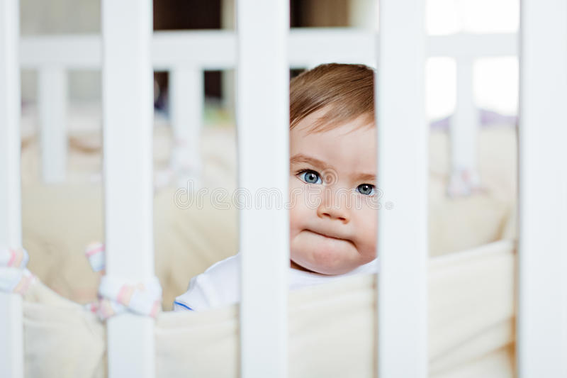 Little cute adorable little blond boy in a striped bodykit sitting with pursed lips behind bars white cot royalty free stock photos