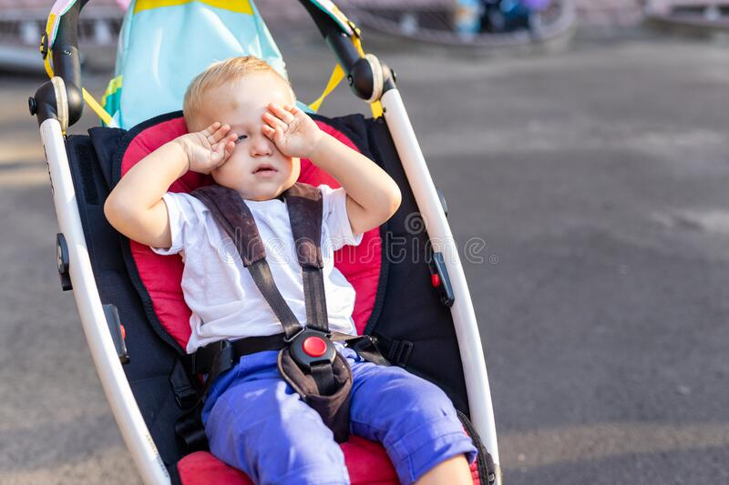 Little cute adorable toddler kid boy rubbing eyes with hands sitting in stroller on bright summer day outdoors. Tired royalty free stock photos