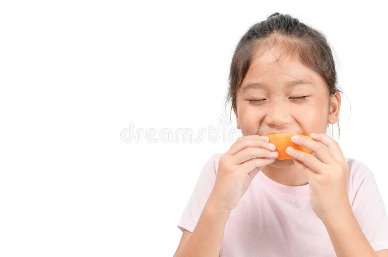 Little cute asian girl enjoy eating sliced orange stock images