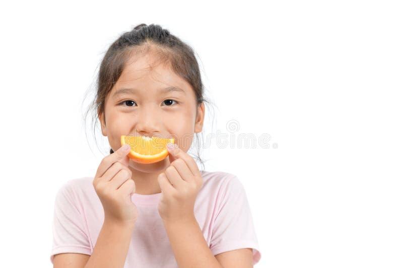Little cute asian girl holding a sliced orange stock images