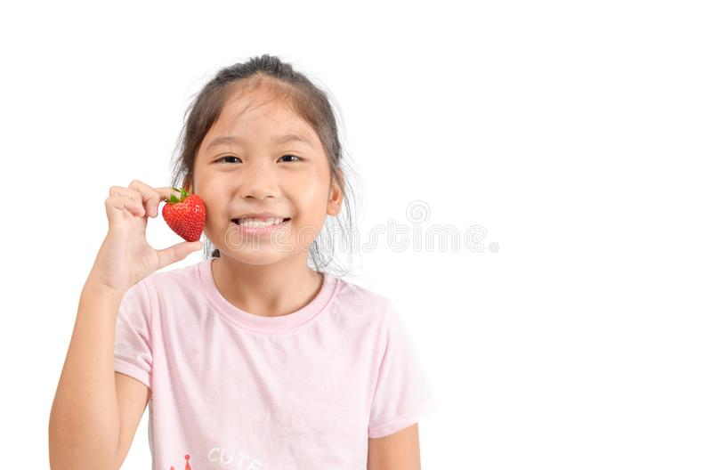 Little cute asian girl holding a strawberry stock photography