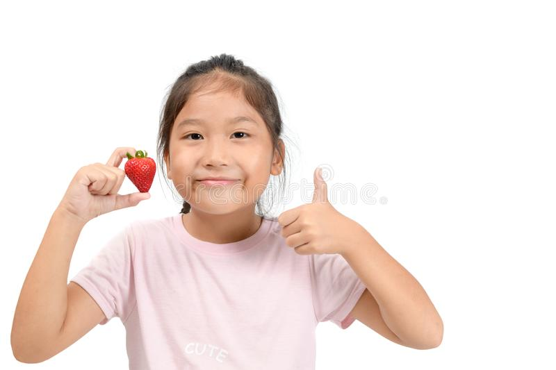 Little cute asian girl holding a strawberry and showing thumb up stock images