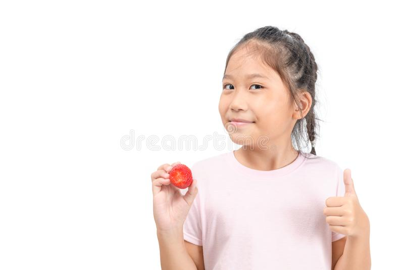 Little cute asian girl holding a strawberry and showing thumb up royalty free stock photography