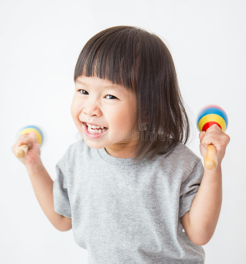 Little cute asian girl playing the maracas royalty free stock photography