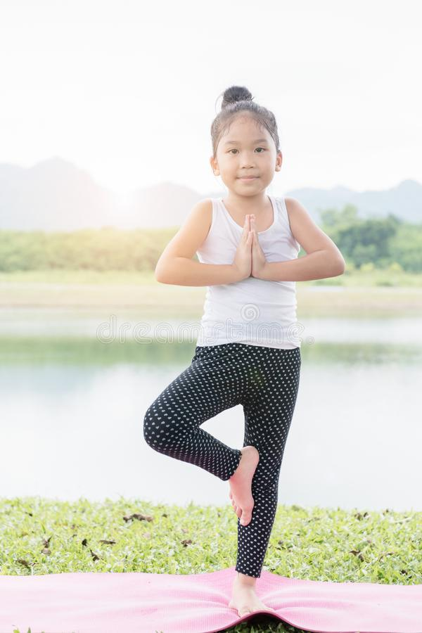 Little cute asian girl practicing yoga pose royalty free stock photos