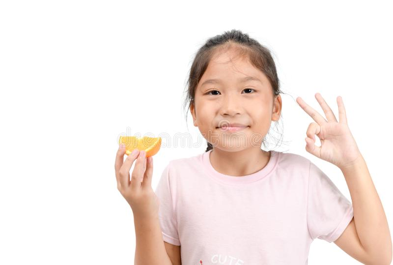 Little cute asian girl smile and holding a sliced orange royalty free stock image