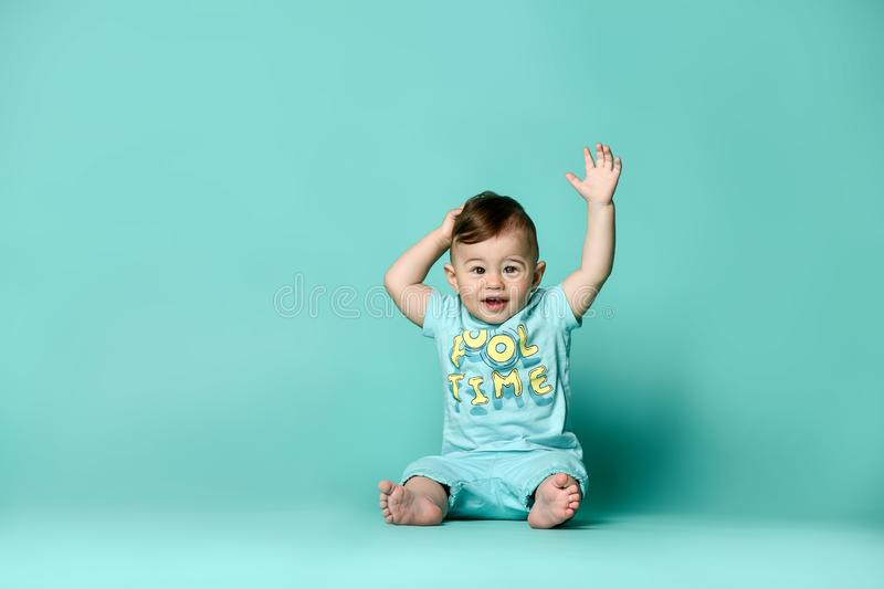 Little cute baby in blue t-shirt isolated. Little cute boys baby sits on the floor in the studio in a summer cotton suit in shorts and a t-shirt, on a turquoise royalty free stock photo