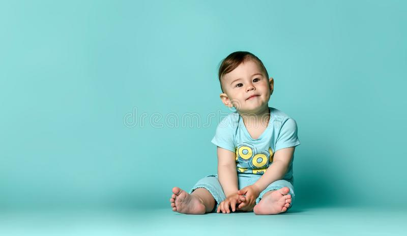 Little cute baby in blue t-shirt isolated. Little cute boys baby sits on the floor in the studio in a summer cotton suit in shorts and a t-shirt, on a turquoise stock photography