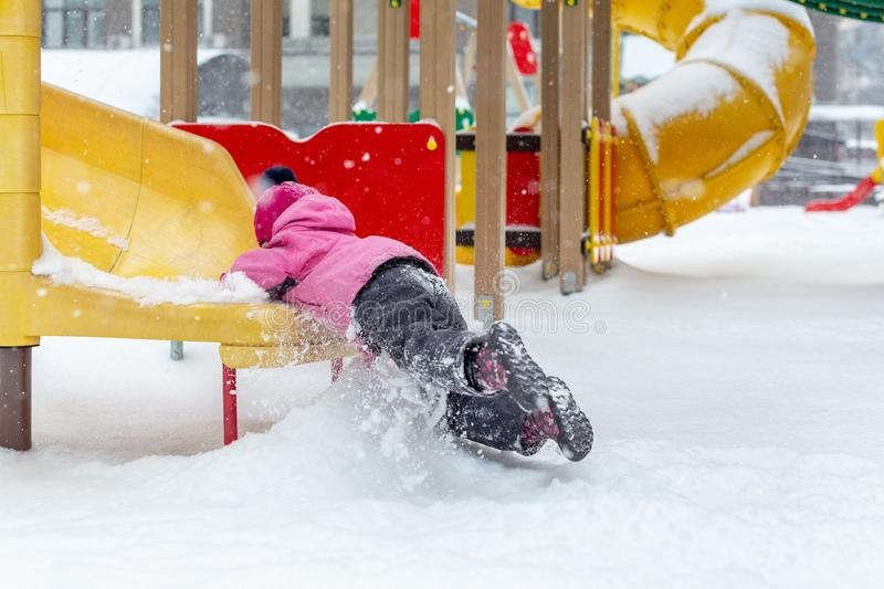 Little cute baby girl having fun on playground at winter. Children winter sport and leisure outdoor activities.  stock photos