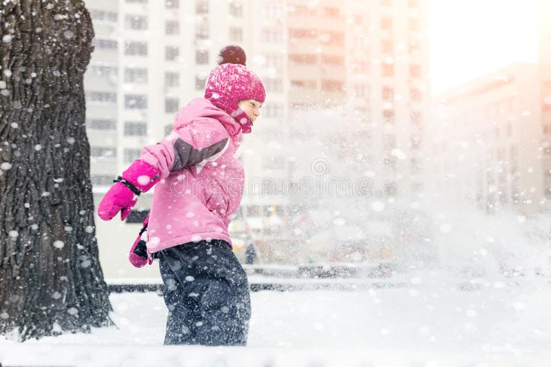 Little cute baby girl having fun on playground at winter. Children winter sport and leisure outdoor activities.  stock photo