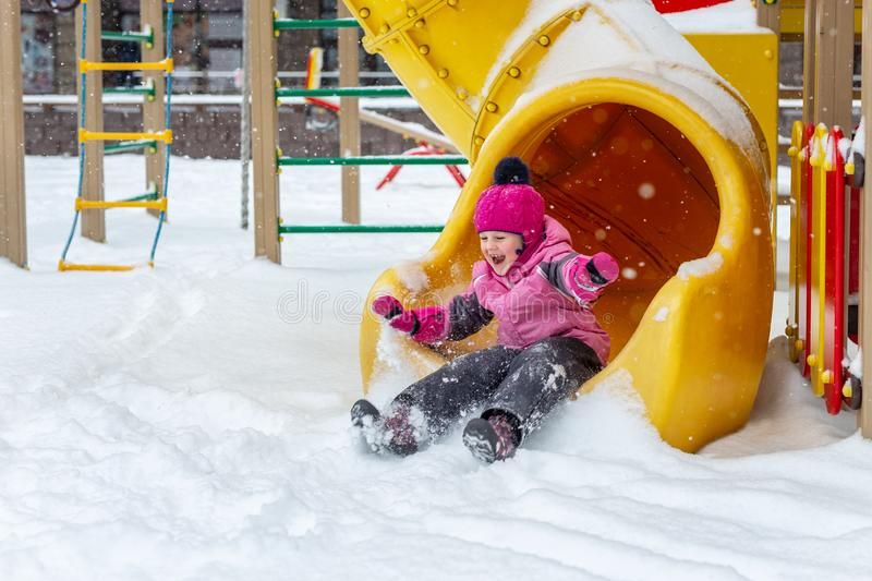 Little cute baby girl having fun on playground at winter. Children winter sport and leisure outdoor activities royalty free stock images