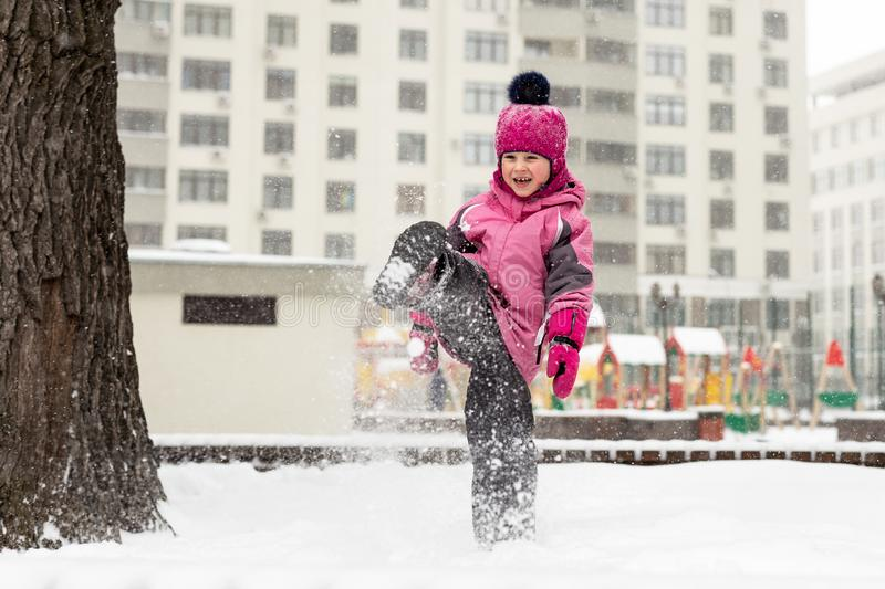 Little cute baby girl having fun on playground at winter. Children winter sport and leisure outdoor activities.  royalty free stock photos