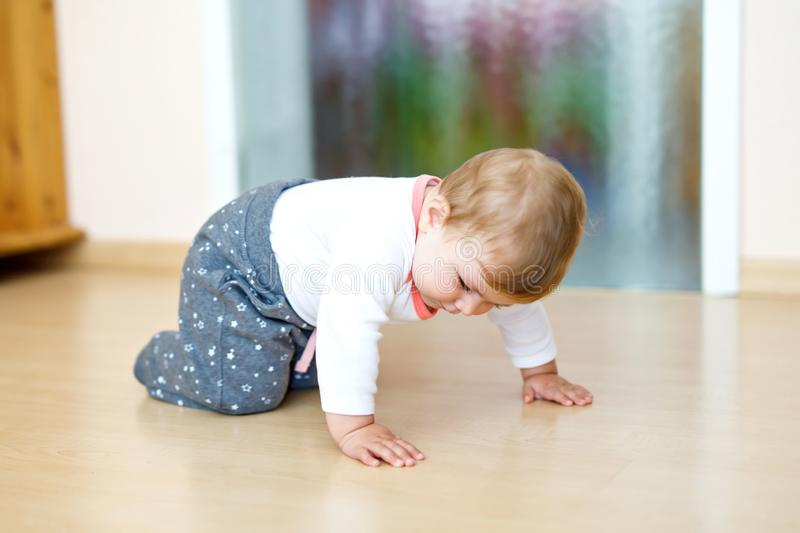 Little cute baby girl learning to crawl. Healthy child crawling in kids room. Smiling happy healthy toddler girl. Cute royalty free stock images