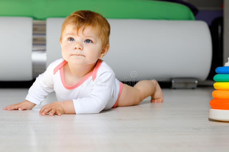 Little cute baby girl learning to crawl. Healthy child crawling in kids room. Smiling happy healthy toddler girl. Cute. Toddler discovering home and learning royalty free stock photo