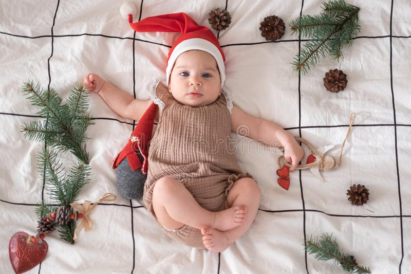 Little cute baby girl portreit in red christmas santa hat with lights top view. Christmas holidays concept. Little cute baby girl portreit in red christmas santa stock image