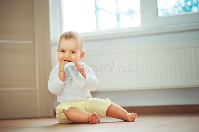 Little cute baby girl sitting in room on floor drinking water from bottle and smiling. Happy infant. Family people indoor Interior royalty free stock images
