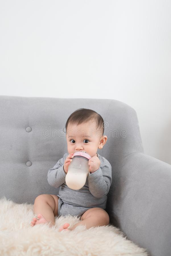 Little cute baby girl sitting in room on sofa drinking milk from bottle and smiling. Happy infant. Family people indoor Interior. Concepts. Childhood best time royalty free stock image