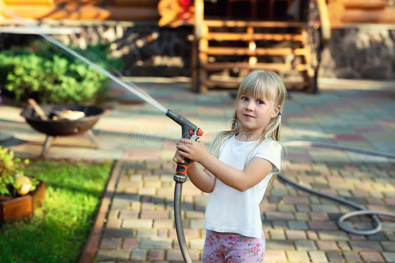 Little cute baby girl watering fresh green grass lawn mear house backyard on bright summer day. Child having fun playing with. Water hose sprinkler garden kid royalty free stock image