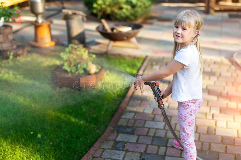 Little cute baby girl watering fresh green grass lawn mear house backyard on bright summer day. Child having fun playing with. Water hose sprinkler garden kid royalty free stock photos