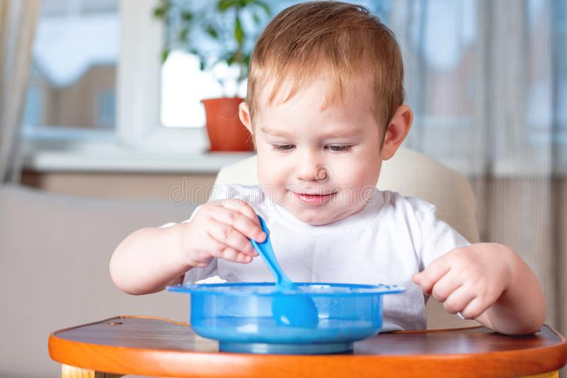 Little cute baby learning to eat with a spoon himself at the kids table in the kitchen. Healthy baby food. Little baby boy learning to eat with a spoon himself royalty free stock image