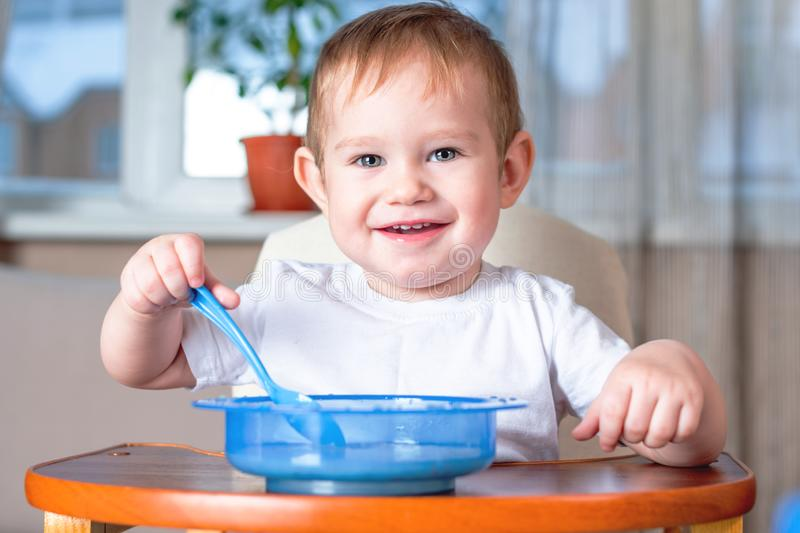 Little cute baby learning to eat with a spoon himself at the kids table in the kitchen. Healthy baby food. Little baby boy learning to eat with a spoon himself royalty free stock images