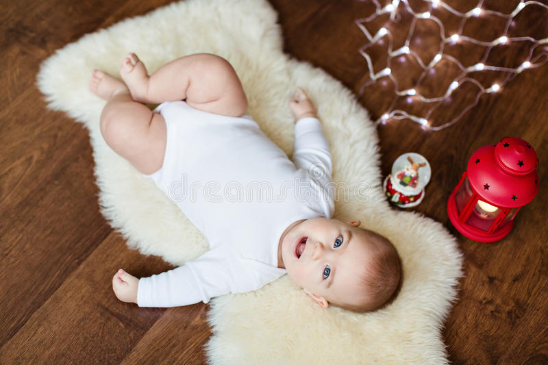 Little cute baby lying on the white skin of the background light royalty free stock photos