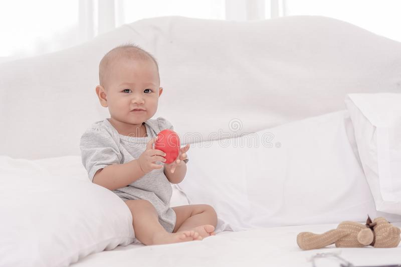 Little cute baby one year girl sitting and playing alone on white bed stock photography