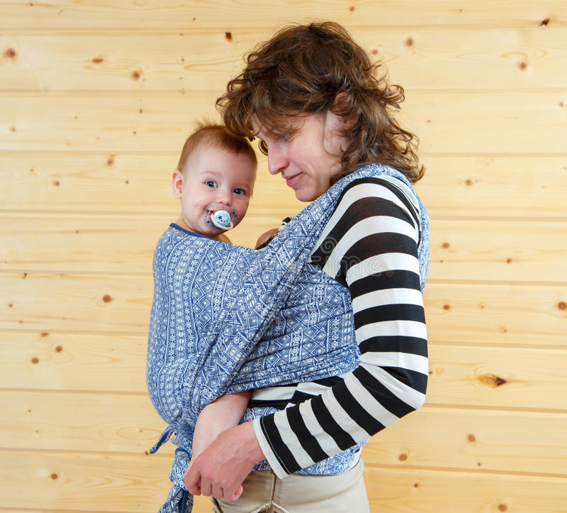 Little cute baby with soother in carrying sling stock photo