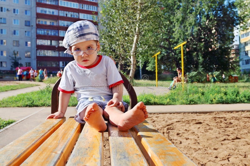 Little cute barefoot boy in glasses royalty free stock image