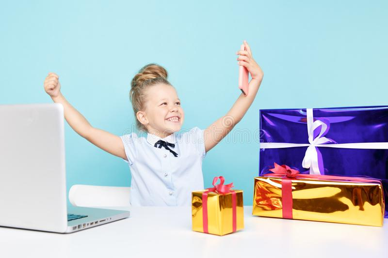 Little cute blogger making selfie on the phone sititng with a lot of presents on the table. royalty free stock photography