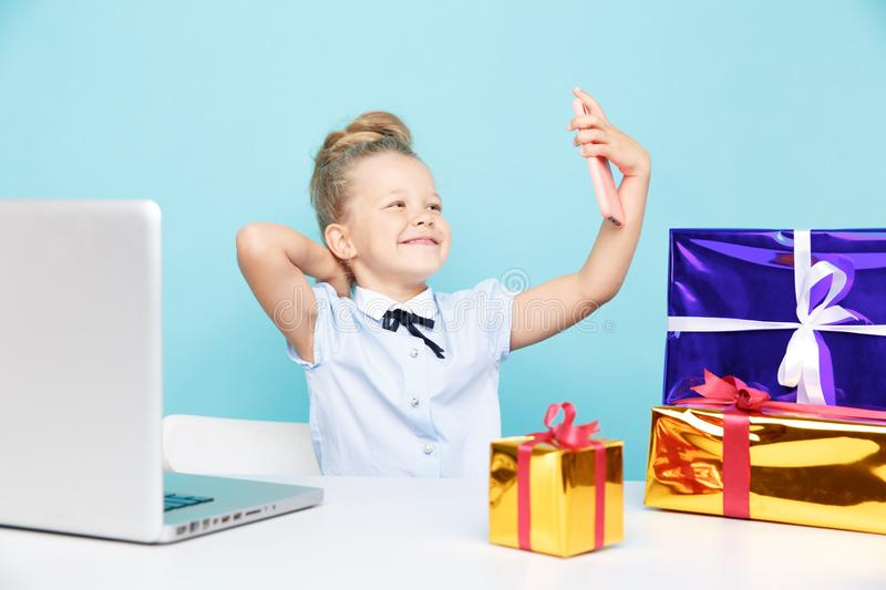 Little cute blogger making selfie on the phone sititng with a lot of presents on the table. stock photography