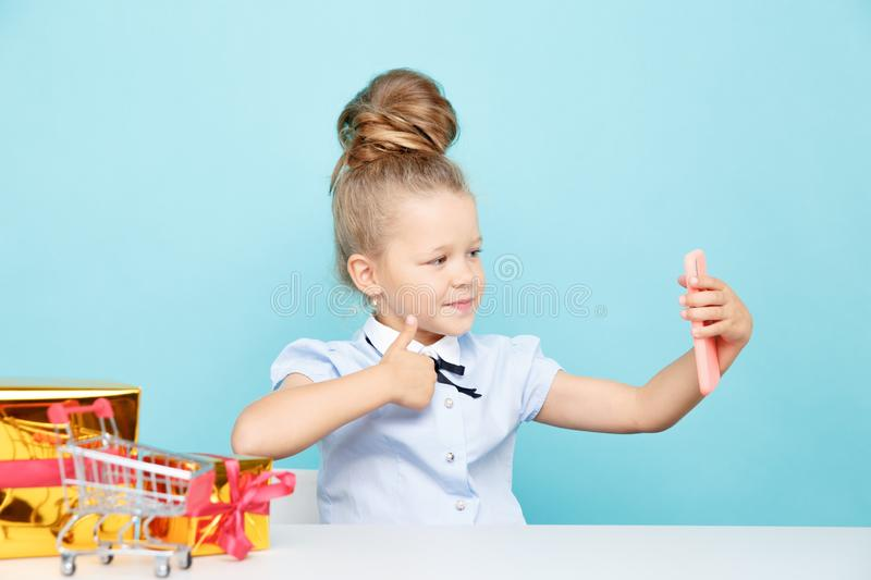 Little cute blogger making selfie on the phone sititng with a lot of presents on the table. stock photos