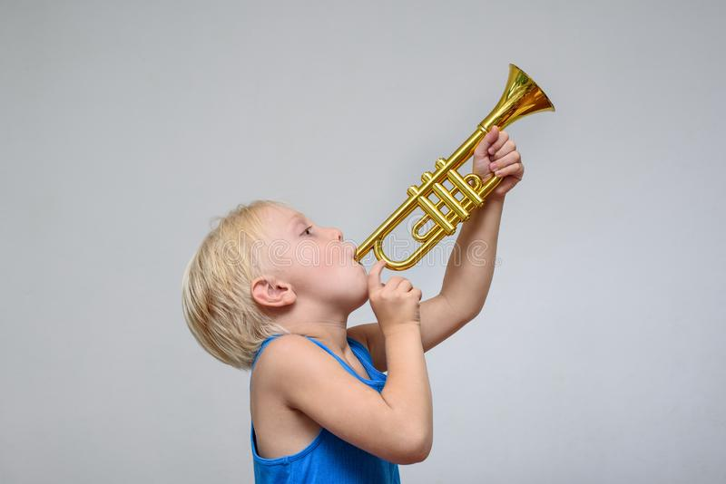 Little cute blond boy playing toy trumpet on light background royalty free stock photo