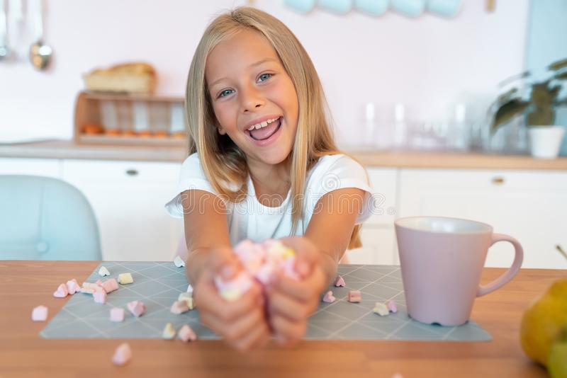 Little cute blond girl in the kitchen having her breakfast having fun with marshmallow and smiling. This is so tasty.  stock photos