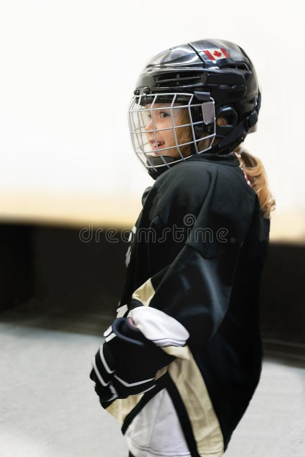 Little cute blonde Canadian 3-years old girl plays hockey in full hockey equipment stock photo