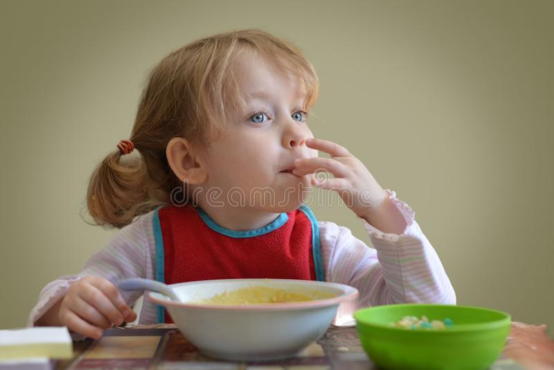 The Little cute blonde curly hair Caucasian girl is seating on the table and eating. She is looking at the window. royalty free stock images