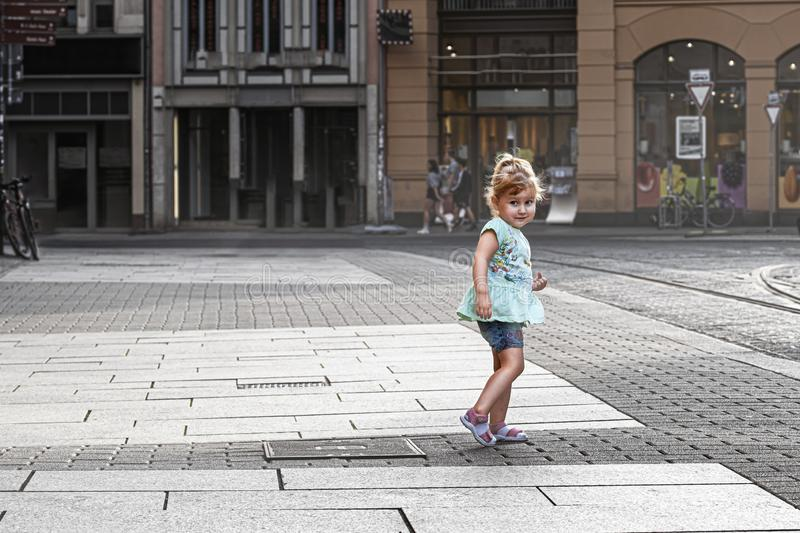 Little cute blonde girl child standing in the town square royalty free stock images