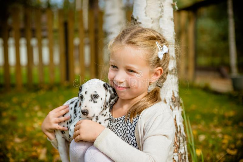 Little cute blonde girl playing with her Dalmatian puppy outdoo, on sunny warm autumn day.care of Pets concept. Child royalty free stock photos